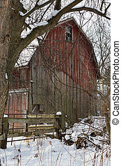 Red Barn - Faded and weather-worn red barn framed by the...