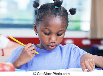 Afro american female student doing school work in classroom