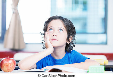 Kid at school desk thinking looking upward