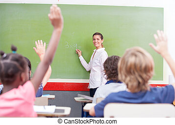 Intelligent group of young school children raising their hands i