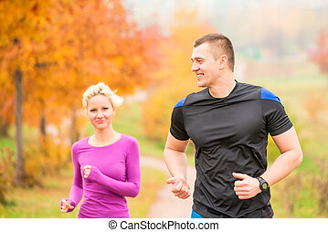 healthy lifestyle - jogging a man and a woman running in the...