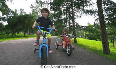 Real Fun - Handheld shot of two little cyclists approaching...