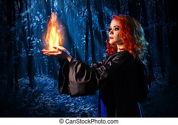 Witch in the night forest holds fire