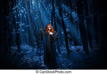 Witch with staff in night forest - Young witch with staff in...