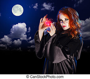 Witch with potion on night sky background - Young witch with...