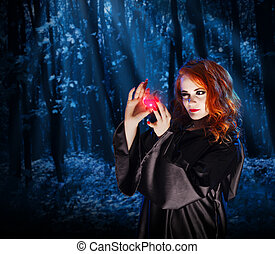Witch with potion at night forest - Young witch with potion...