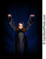 Witch girl on blue rays of light background - Young witch...