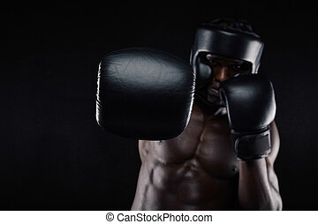 Young muscular man practicing boxing. African male throwing...