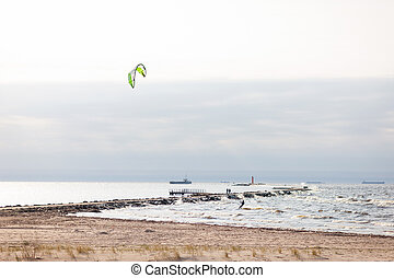 Kiteboarders to sail the lighthouse in the sea with ships in...