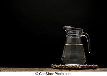 Natural water in a glass jar on a black background