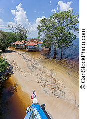 Beach with neglected cabins in the middle of Rio Negro,...