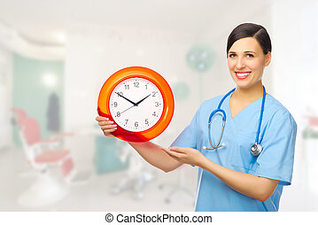 Young doctor with clock on clinic