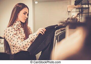 jonge, vrouw, kies, kleren, op, Een, rek, in, Een, showroom,...