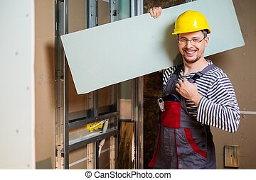 Builder with plasterboard in new building interior
