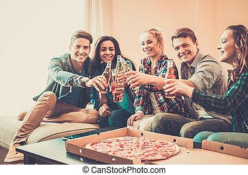 Multi-ethnic friends with pizza and bottles of drinks having...