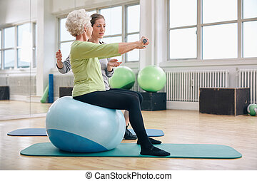 Female trainer assisting senior woman lifting weights in...