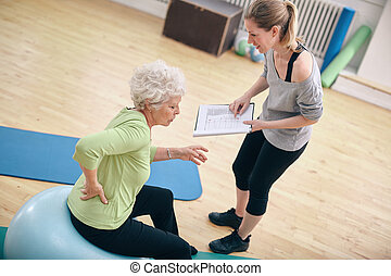 Physical therapist with old woman at rehab