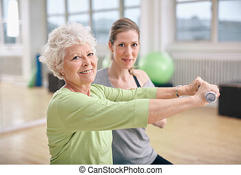 Fitness training with a personal trainer at gym - Senior...
