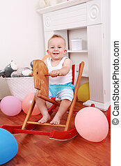 Rocking horse ride - Cute smilling boy enjoy his rocking...