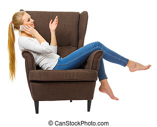 Young woman talking by mobile phone in chair isolated