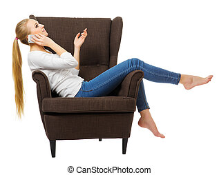 Young girl with mobile phone on chair isolated
