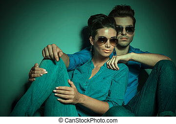 Young fashion man siting near his girlfriend, embracing her...