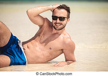 Smiling young man lying on the beach