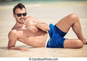 Hot young man lying on the beach