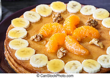 Homemade pastry cake with bananas , tangerines and condensed...