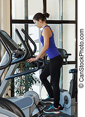 Gym woman workout - Woman doing exercises with elliptical...
