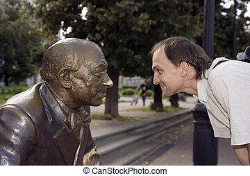 Eyes in eyes - The young man looks in the face to a statue