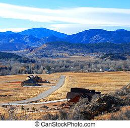 Rural Scene - Rural houses dotting a valley below purple...