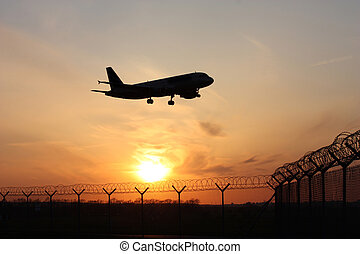 Airplane landing at sunset - Plane landing at the airport at...