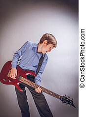 teenager boy of 10 years European appearance playing guitar...