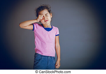 girl child rubs his eyes on gray background cross process -...