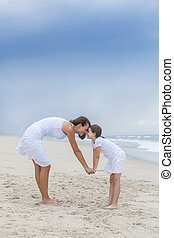 Woman and Child, Mother, Daughter Rubbing Noses On Beach - A...