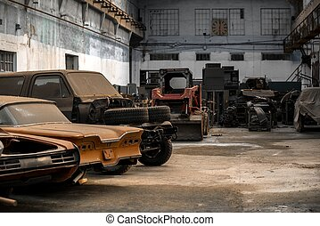 Abandoned old cars in empty factory closeup