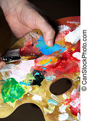 Artist paints a picture - Artists hand holding a paintbrush...