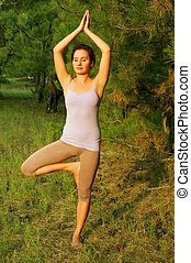 """Girl standing in the """"tree pose"""" on the grass in the forest"""