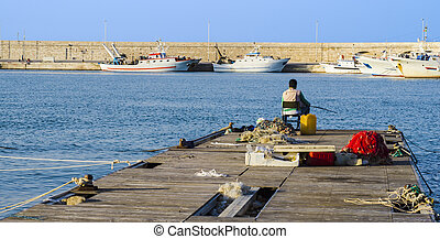 Fisherman sitting on the dock of a port