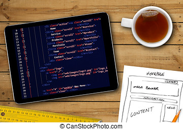 website wireframe sketch and programming code on digital...