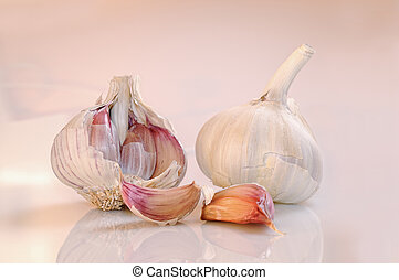 garlic on a white and pinkish base - two heads of garlic on...