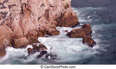 ocean waves lapping on the shore rocks