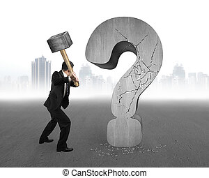 businessman holding hammer cracked question mark with gray...
