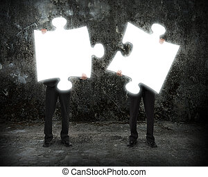 Glowing puzzles businessmen hold to connect illuminating...