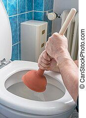 Unblocking a Toilet with a Plunger - A plumber using a...
