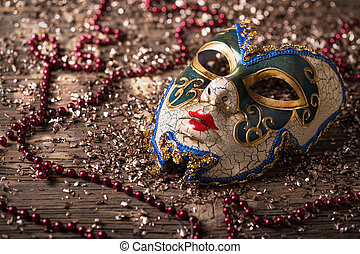 Carnival mask with red necklace on wooden background