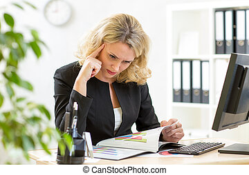 middle-aged business woman working in office and examining...