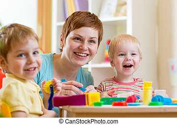 woman playing and teaching children - woman teaches children...