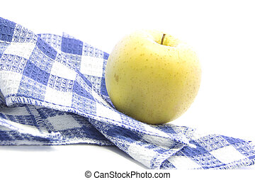 Fresh yellow apple healthy fruit on blue tablemat and white...